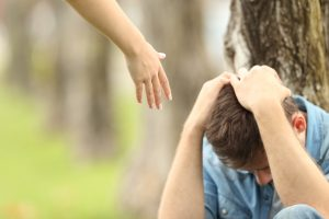 Hand Reaching to Upset Teen Boy