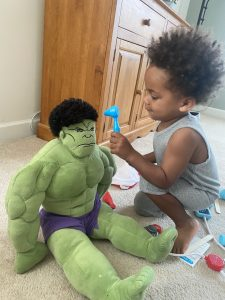 Child Playing Doctor, Looking in Stuffed Hulk's Ears